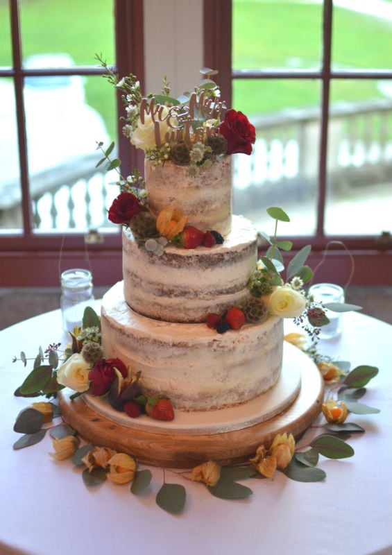 Semi-naked wedding cake at Lulworth Castle. Cake flavours base lemon, chocolate & Victoria at the top.