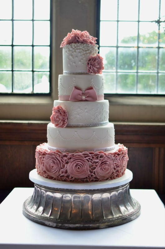Dusky pink ruffles and lace wedding cake at Rhinefield House.