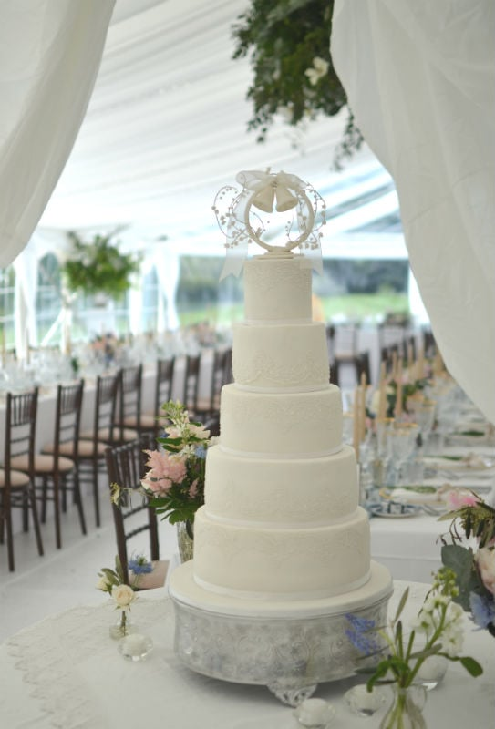 Five tier white wedding cake with lace and handmade sugar topper at Smedmore House.