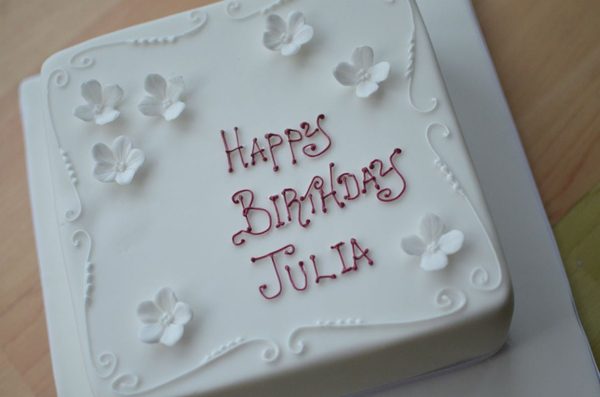 White birthday cake with blossom.
