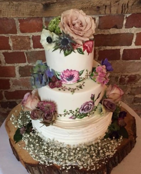 Hand painted wedding cake with fresh flowers at Highcliffe Castle