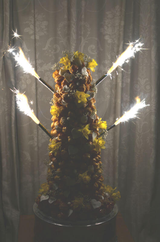 Croquembouche lit with fountain candles.
